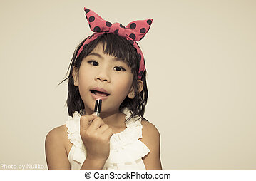 Cute Asian child making up her face with lipstick