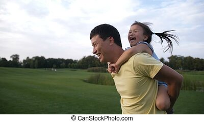 Cute asian daughter on piggyback ride with her dad