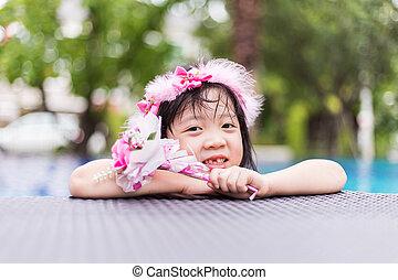 Cute Asian girl at swimming pool