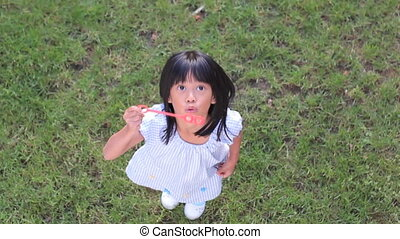 Cute Asian Girl Blowing Bubbles - A cute little 6 year old...