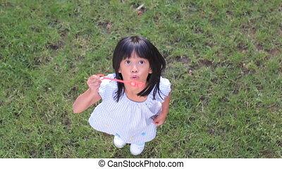 Cute Asian Girl Blowing Bubbles