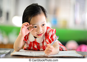Cute Asian girl doing her homework.