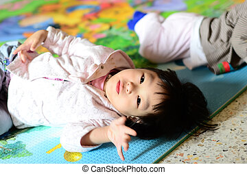 Cute Asian girl lying on the floor and look at camera.