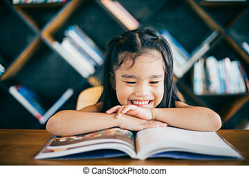 Cute asian girl reading a book and smiling teeth white while...