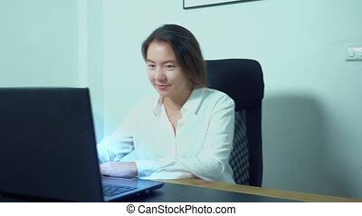 cute asian girl use laptop at table in office