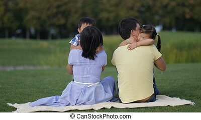 Cute asian kids tenderly embracing parents in park