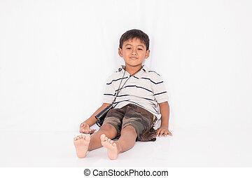 Cute asian little boy sitting on floor with binoculars