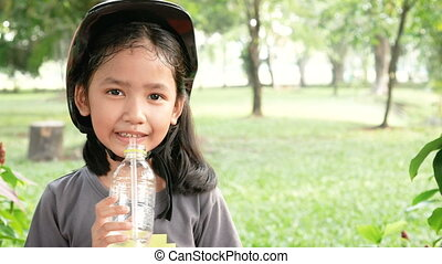 Cute Asian little girl drinking water with happiness at nature park