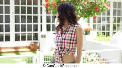 Cute Asian woman in tied plaid shirt leaning near fence...