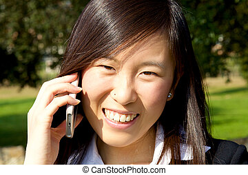 Cute asian woman on the phone smiling happy