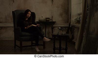Cute asian woman reading a book in retro interior