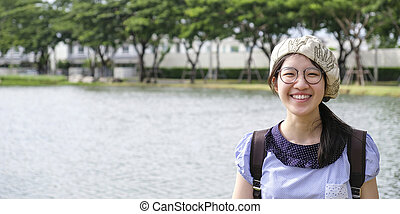 Cute asian woman wearing glasses smiling in the garden