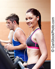 Cute athletic woman standing on a running machine with earphones in a fitness center