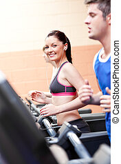Cute athletic woman with earphones exercising on a running machine in a fitness center
