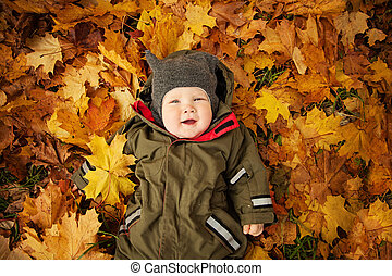 Cute Autumn Child on Fall Yellow Leaves, top view