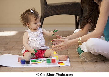 Cute baby and mom painting outside