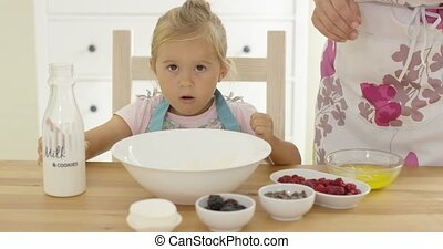 Cute baby baking with woman in a kitchen