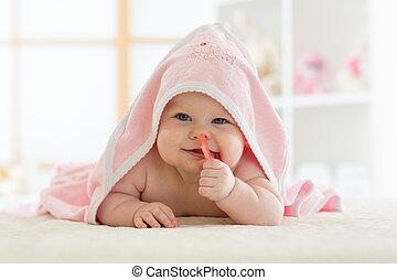 Cute baby biting teether under a hooded towel after bath