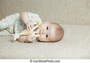 Cute baby biting toy giraffe