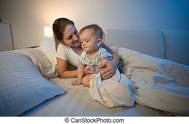 Cute baby boy and his mother in bed at late night