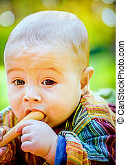 Cute baby boy biting a wooden toy