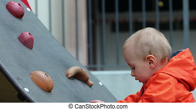 Baby Boy Climbing On A Wall At A Park