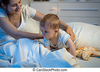 Cute baby boy crawling on bed at night