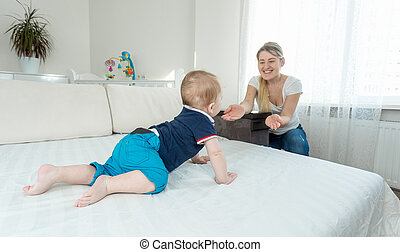 Cute baby boy crawling on bed to happy young mother