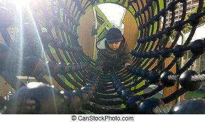 Baby Boy Crawling Through A Rope Tunnel Bridge