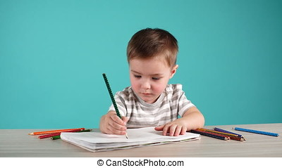 Cute baby boy drawing with pencils in album on blue...