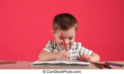 Cute baby boy drawing with pencils in album on pink...