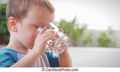 Cute baby boy drinking a glass of water in a cafe. Slow motion little boy drinking water. Close-up. The child is drinking a cup of water.