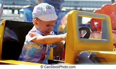 Cute baby boy drives on yellow toy car in the attraction park on sunny summer day. 3840x2160