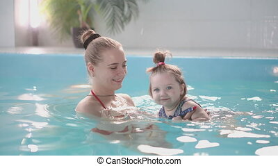 Cute baby boy enjoying with his mother in the pool. - Cute...