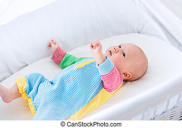Cute baby boy in a white crib - Newborn baby boy playing in...