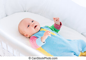 Cute baby boy in a white crib