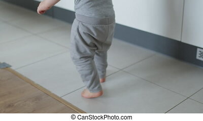 Cute baby boy in gray outfit making his first steps . High quality 4k footage