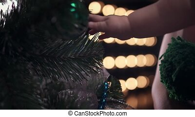 Cute baby boy in striped cap shoots a green ball toy from a Christmas tree. Close-up