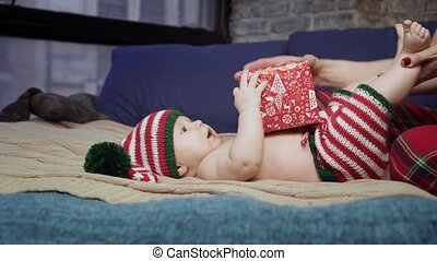 Cute baby boy is lying on back, playing with his mother and trying to open red gift box