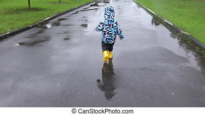 Cute baby boy is runing in puddle - Cute baby boy is playing...