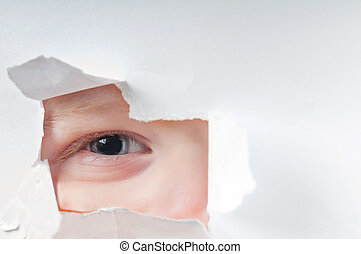 Cute baby boy looking through paper hole