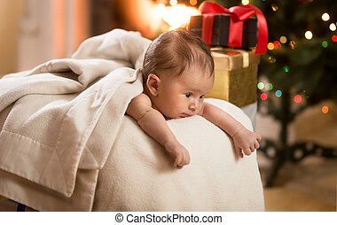 cute baby boy lying in basket next to Christmas tree