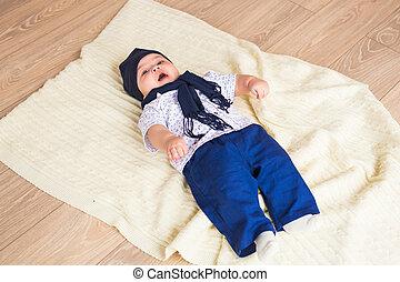 Cute baby boy lying on a floor