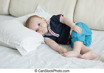 Cute baby boy lying on big pillow on bed