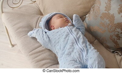 Cute baby boy lying on the couch