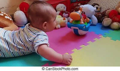 cute baby boy on his tummy trying to reach toys