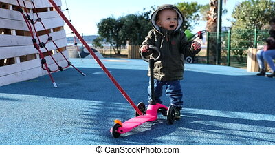 Cute Baby Boy Playing With A 3 Wheel Scooter