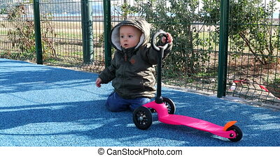 Baby Boy Playing With A 3 Wheel Scooter