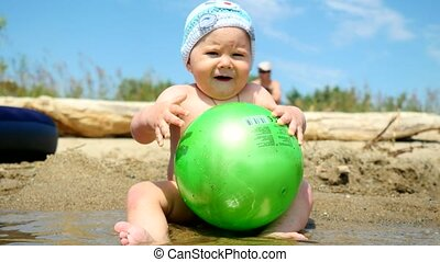 Cute baby boy playing with a ball on the beach