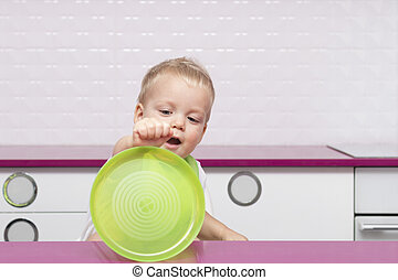 Cute baby boy playing with a green plastic plate in the modern white kitchen. Funny toddler showing his empty plate.